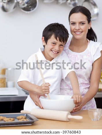 Smiling mother and son having fun in the kitchen