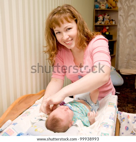 Smiling mother cares newborn baby