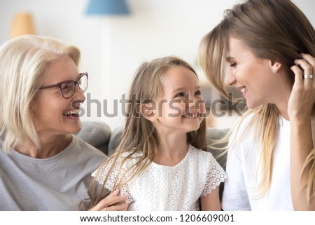 Smiling mother, daughter and grandmother sit on cozy couch at home having fun, three generations of women hugging enjoy spending time together, family of mom, granny and child relax indoors laughing