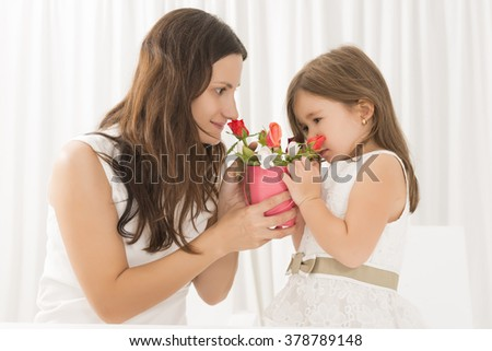 Smiling mother getting flowers from her daughter on mother's Day.Toddler girl giving flowers to her mom on mother's day. Happy family concept #378789148