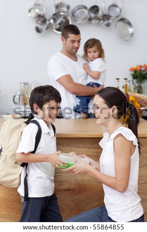 Smiling mother giving school lunch to her son in the kitchen