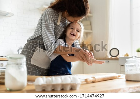 Smiling mother having fun with small preschool kid daughter, playing with dough in kitchen. Happy adorable little child girl in apron enjoying cooking homemade pastry together with mommy at home.