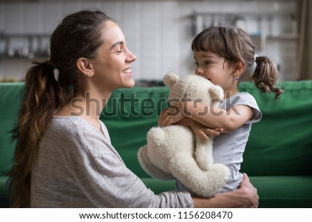Smiling mother hugging cute little girl holding teddy bear toy showing love and care in family, young mom embracing protecting child, sincere relationships between mum and daughter cuddling concept