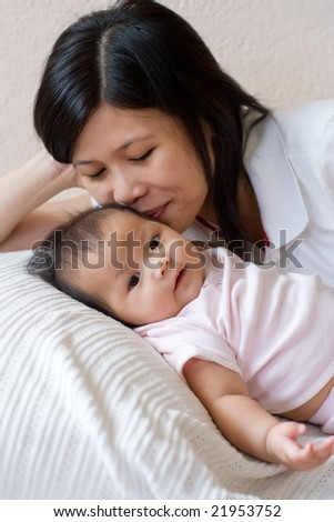 Smiling mother kissing her baby's head