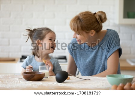 Smiling mother looking at little daughter and feeding her after bake cookies standing at table in kitchen. Happy caring mum and adorable girl eating flour and drink milk, preparing dinner.