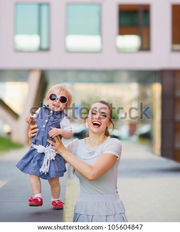 Smiling mother playing with baby in city