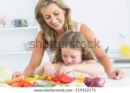 Smiling mother teaching her daughter how to prepare vegetable