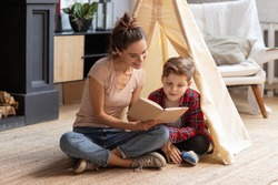 Smiling mother tell fairytale to son at home. Good family pastime on weekend. Adopted child and baby sitter. Mom read interesting story schoolboy kid. Wigwam in cozy living room. Educational process