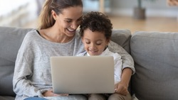 Smiling mother with African American son using laptop close up, happy mum and preschool child sitting on sofa at home, watching cartoons online or play video game, family having fun