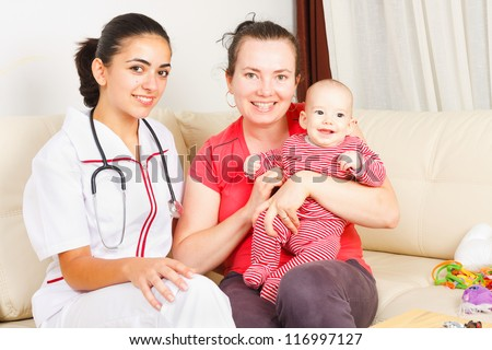 Smiling mother with her happy son are sitting next to a kind nurse.