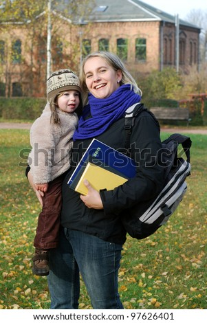 smiling mother with school equipment carries her daughter