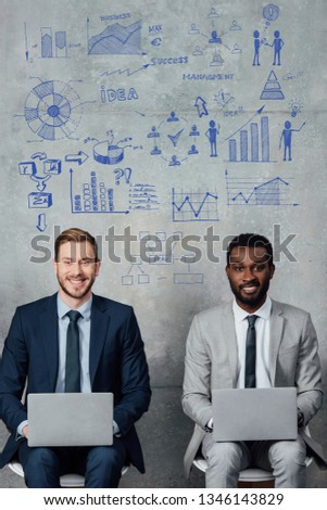 smiling multiethnic businessmen looking at camera and using laptops in waiting hall with business development illustration on wall