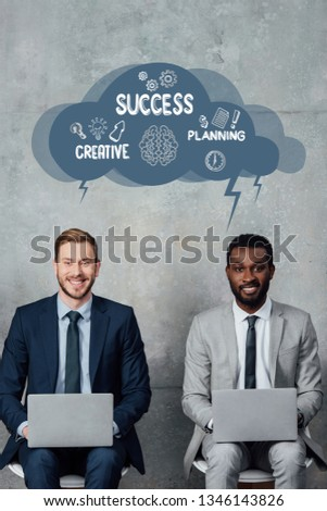 smiling multiethnic businessmen looking at camera and using laptops in waiting hall with speech bubble illustration with creative, success and planning lettering