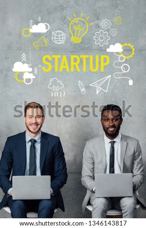 smiling multiethnic businessmen looking at camera and using laptops in waiting hall with startup illustration on wall