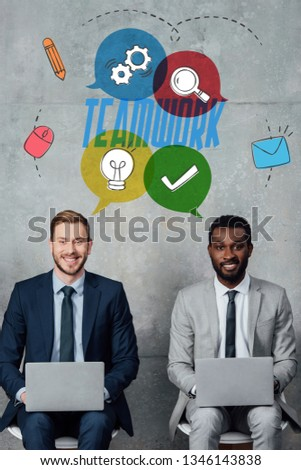 smiling multiethnic businessmen looking at camera and using laptops in waiting hall with teamwork lettering on wall