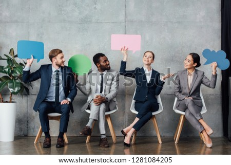 smiling multiethnic businesspeople holding speech bubbles and thought bubble while sitting in waiting hall