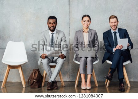 smiling multiethnic businesspeople reading newspaper and using digital devices in waiting hall
