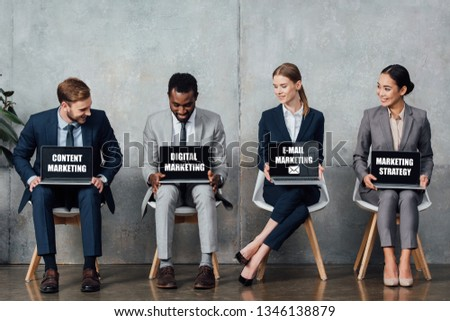 smiling multiethnic businesspeople sitting on chairs and holding laptops with content, digital, e-mail marketing and marketing strategy lettering on screens in waiting hall