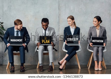 smiling multiethnic businesspeople sitting on chairs and holding laptops with plan, strategy, management and motivation words on screens in waiting hall