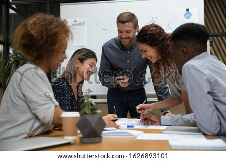 Smiling multiethnic colleagues busy working on paperwork discussing project business ideas in office together, happy diverse coworkers brainstorm consider strategies at meeting, cooperation concept