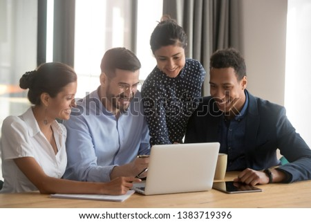 Smiling multiethnic employees sit at office desk look at laptop screen cooperating in office, happy diverse colleagues laugh watching funny video on computer, brainstorm together at meeting