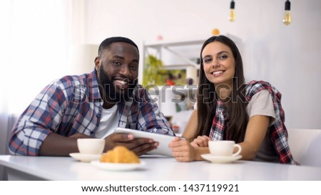 Smiling multiethnic family using tablet during breakfast, looking at camera