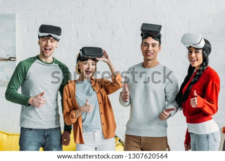 smiling multiethnic friends putting on virtual reality headsets and showing thumbs up
