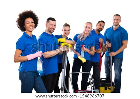 Smiling Multiethnic Group Of Janitors Wearing Blue T-shirt Standing Grouped Together With Their Equipment