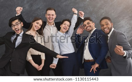 Smiling multiethnic group posing and having fun. Business colleagues shooting for company ad. Concept of teamwork, unity