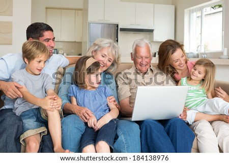 Smiling multigeneration family using laptop in living room #184138976