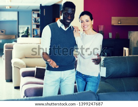 Smiling multinational couple is choosing new furniture for interior their room in the store