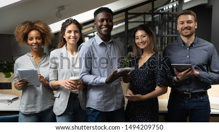 Smiling multiracial business team with african male leader standing together looking at camera in office, happy international diverse employees professionals company staff group corporate portrait