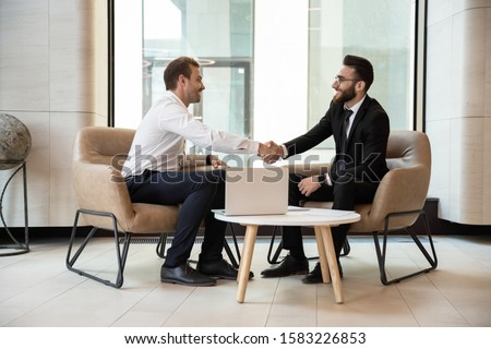 Smiling multiracial businessmen shake hands closing successful business deal at office briefing, diverse male partners handshake get acquainted greeting at meeting, partnership, cooperation concept
