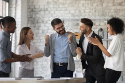 Smiling multiracial businesspeople congratulate colleague with job success or achievement. Happy supportive diverse multiethnic employees greet excited male worker with work promotion.