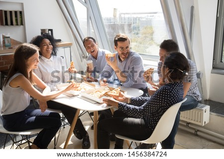 Smiling multiracial colleagues have fun spending work break enjoy eating pizza in office, happy diverse employees chat tasting Italian takeaway food, celebrate special occasion, talking and laughing