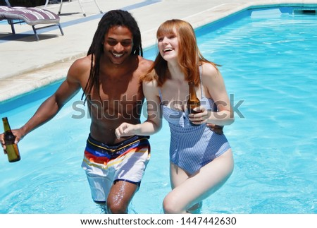 Smiling multiracial couple drinking beer - Redheaded girl and her black boyfriend on vacation #1447442630