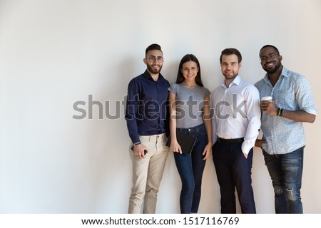 Smiling multiracial group of international company workers standing in line near white wall. Successful young team members ready to work, portrait. Confident diverse business people looking at camera.
