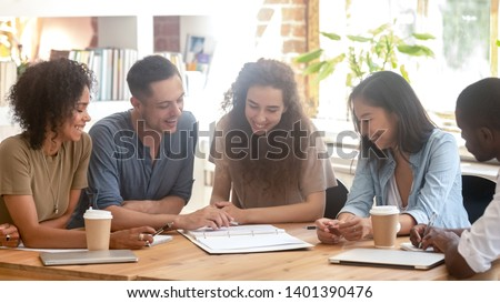 Smiling multiracial millennial people sit at shared office desk look at paperwork discuss issues together, happy diverse company interns collaborate engaged in team brainstorming. Teamwork concept