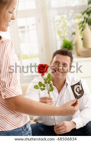 Smiling mum holding ultrasound image of baby, dad giving red rose smiling, sitting on couch.