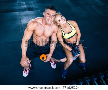 Smiling muscular man and happy sporty woman resting on bench at gym. Looking at camera