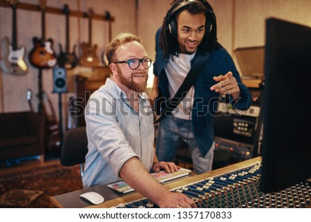 Smiling music producer and a young African American musician with a guitar talking together over a soundboard in a recording studio #1357170833