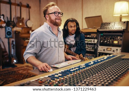 Smiling music producer working on a soundboard while laying down tracks with a guitarist during a recording studio session #1371229463