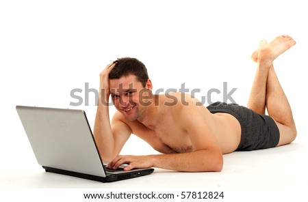 smiling naked man lying on the floor and working on laptop