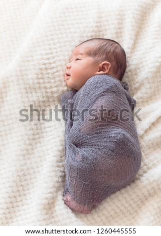 Smiling newborn Asian baby boy swaddled in purple knitted mohair wrap. Lovely portrait of 6 day old infant lying on the bed with cozy blanket background