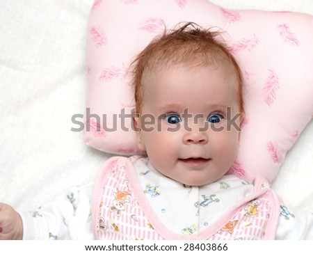 smiling newborn baby girl on pillow close-up