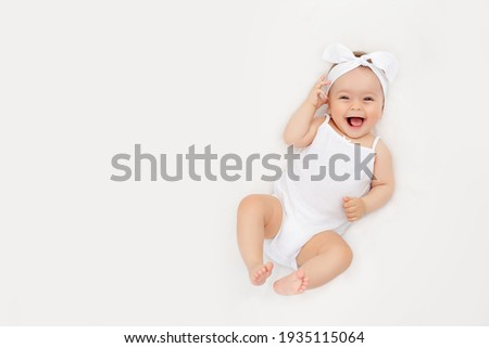 smiling newborn baby on a white bed at home, the concept of a happy, healthy baby, a place for text