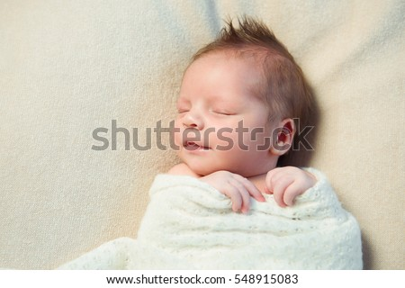 Smiling newborn baby with Mohawk hair sleeping in white blanket.