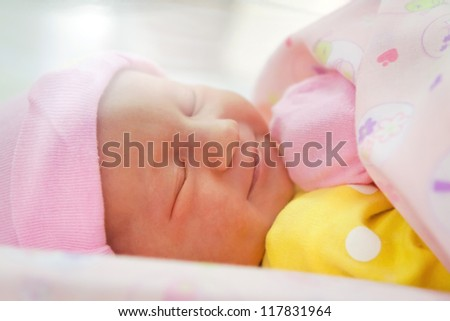 Smiling newborn girl sleeping close-up