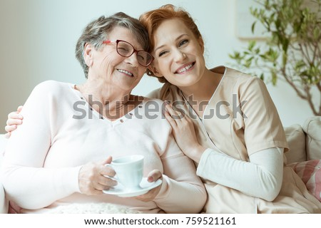 Smiling nurse in beige uniform hugging old lady drinking tea while sitting on white sofa in nursing home