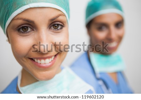 Smiling nurse in surgical cap with other smiling nurse in background